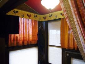Рулонная штора на верхней части двери поднимается. На нижней части, как и на нижней части окна слева, рулонные шторы статичные.