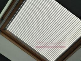 Штора плиссе натяжного типа на окне в потолке. Фиксация справа внизу. Слева вверху подвижный карниз с ручкой управления.