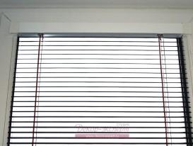 Верхний карниз кассетных горизонтальных жалюзи 16 мм. плотно прилегает к раме пластикового окна. Справа видна цепочка управления.