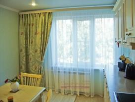 Фото-97.  Штора мятного цвета и молочная вуаль на окне кухонной зоны.