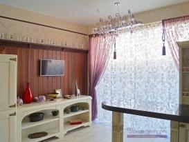 Фото-93.  Вид на легкие шторы основного окна кухни и стену орехового цвета.