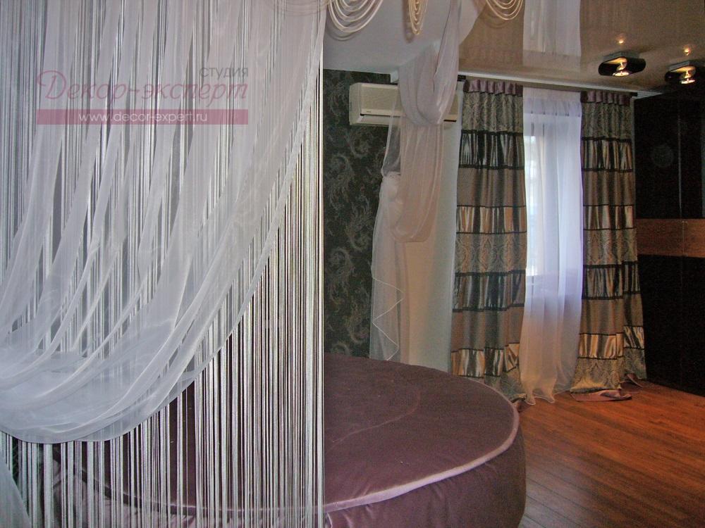 Балдахин над кроватью из драпировок и белой кисеи.