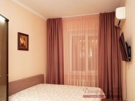 Общий вид спальни с лиловыми шторами в квартире в Тольятти.