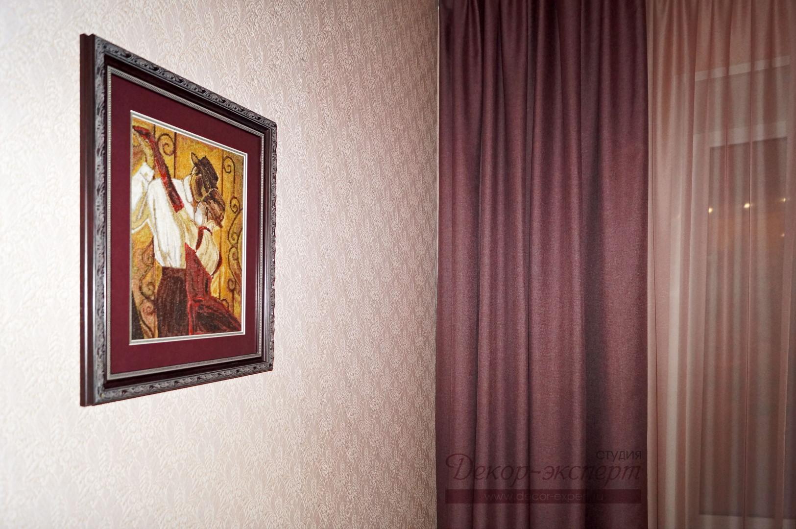 Вышитая картина на стене с обоями в светло лиловых тонах.