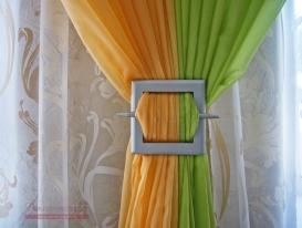 Фото-88. Две тюли-драпировки салатового и оранжевого цвета, подхваченные квадратной серебристой заколкой.