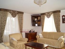 Классические шторы с кантом и ажурным ламбрекеном на смежных угловых окнах гостиной.