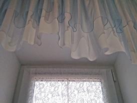 Прямое полотно кружевного тюля закреплено на балконной двери детской комнаты для девочки.