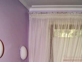 Фрагмент тюля на круглом металлическом карнизе на окне в женской душевой комнате.