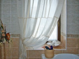 Легкая штора с провисами на круглом карнизе для окна ванной комнаты.