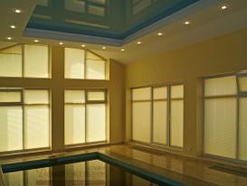 Общий вид штор плиссе на окнах в зале бассейна в загородном доме.