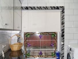 Рулонные шторы LUX в приоткрытом состоянии на окне в постирочной комнате в коттедже.