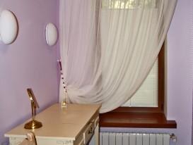 Тюль на круглом металлическом карнизе и штора плиссе на окне в женской душевой комнате.