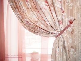 Фрагмент портьеры из хлопковой ткани с принтом на окне у лестницы. Хорошо виден плетёный подхват.