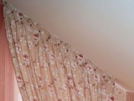 Профильный алюминиевый карниз для штор у лестницы в загородном доме закреплён на скошенном потолке.