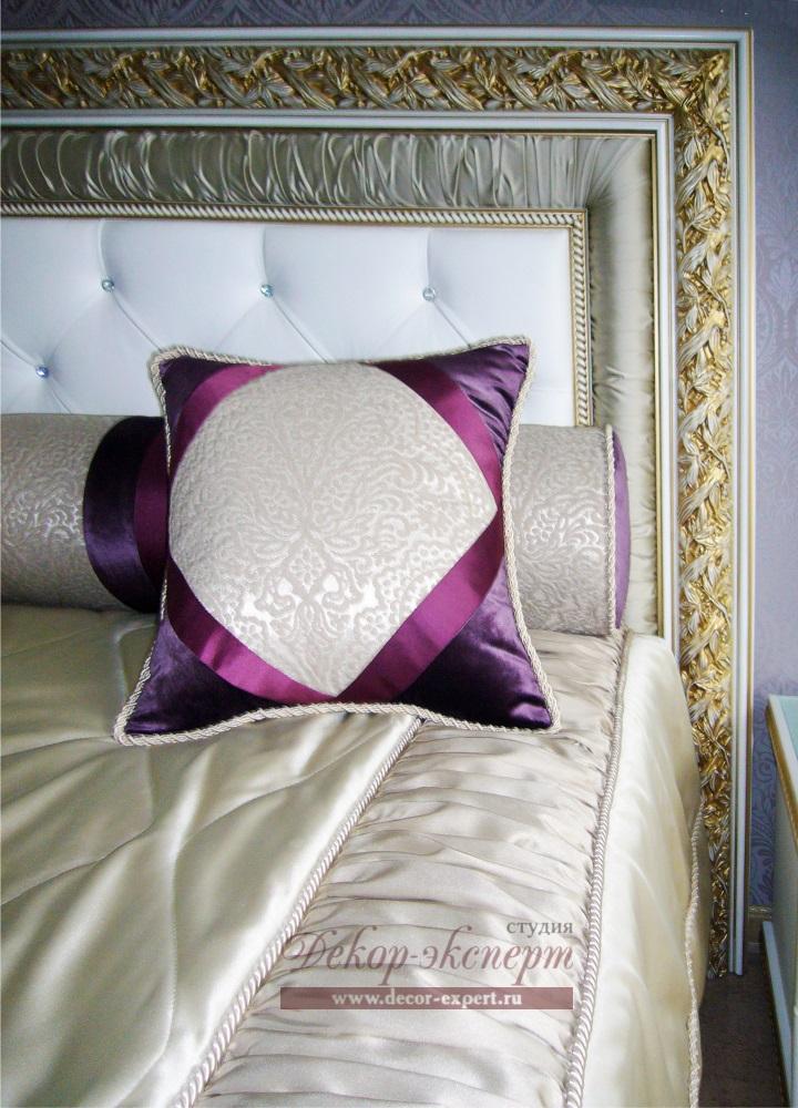 Декоративные валики и подушки на покрывале.