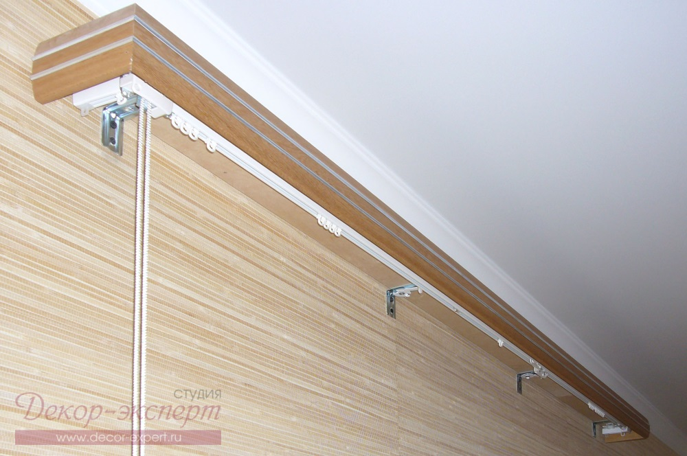 Профильный алюминиевый карниз с багетной планкой с раздвижным механизмом от центра для портьер. На кронштейнах видны клипсы крепления карниза для римской шторы.