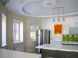 Декоративная штукатурка на стенах, яркий зелёный фартук над кухонной столешницей, оранжевые цвета дверей - элементы интерьера гостиной.