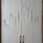 Шкаф со стилизованным рисунком города на дверях.